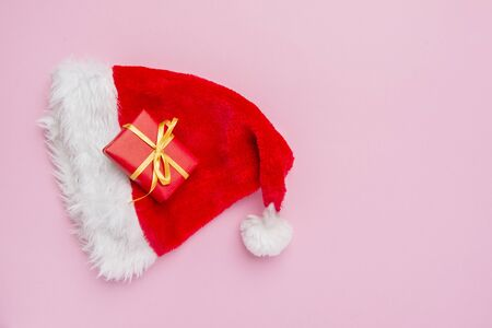 Gift box with santa hat on pink background Stock Photo