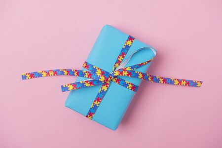 World Autism awareness blue background with gift on pink background.