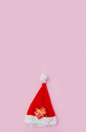 Gift box with santa hat on pink background Stockfoto