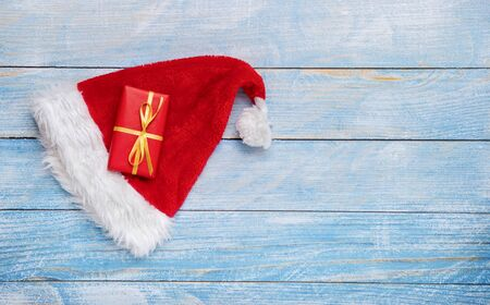 Gift box with santa hat on wooden background Stockfoto
