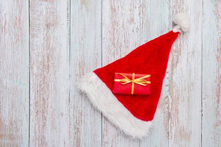 Gift box with santa hat on old wooden background Stockfoto