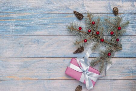 Christmas gift box with decoration on wooden background.