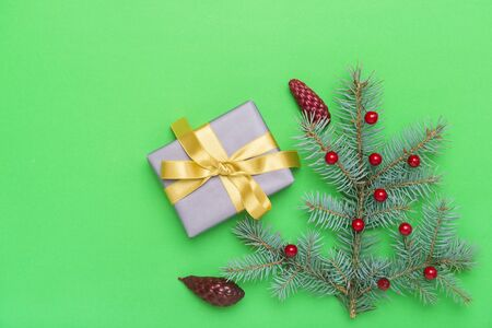 Christmas gift box with decoration on green background. Banco de Imagens