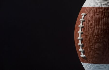 American football ball close up on black background. Stock Photo