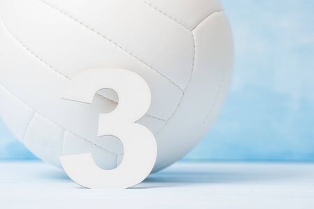 White leather volleyball detail and number three on blue background 免版税图像