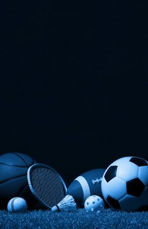 Sports equipment, rackets and balls on green grass with black background and copy space.
