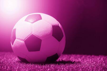 Soccer ball on grass against black background. Pink filter