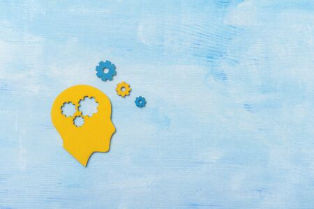 Brain works concept. Thinking, creativity concept of the human head with gears on blue background