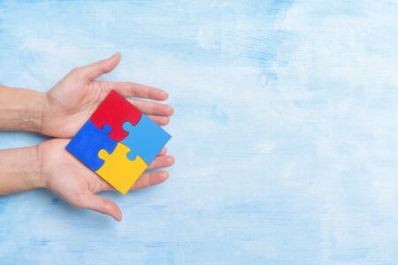 hands playing a puzzle symbol of Public awareness for autism spectrum disorder.
