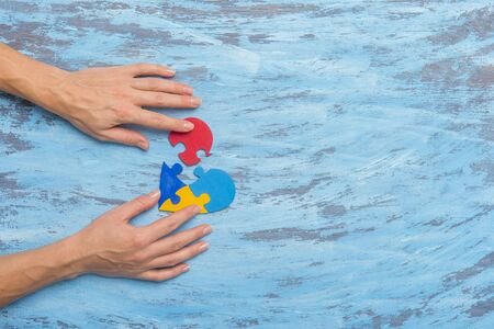 Hand Holding Colorful Heart On Blue Background. World Autism Awareness Day Concept