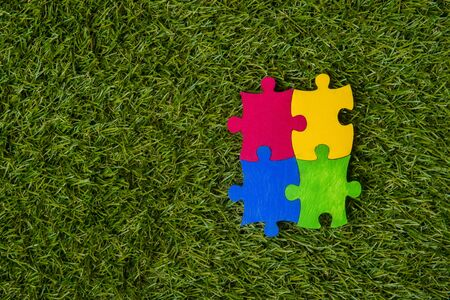 Colorfull puzzles piece on green grass background. World Autism Awareness Day Concept