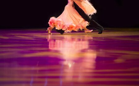 Woman in orange gown and man black tailcoat. Latino dancing
