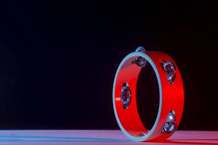 Tambourine isolated on black background.Single classical music instrument. Red neon Banner Art concept