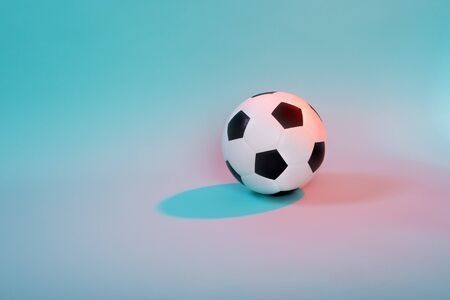 Soccer ball isolated on blue neon background