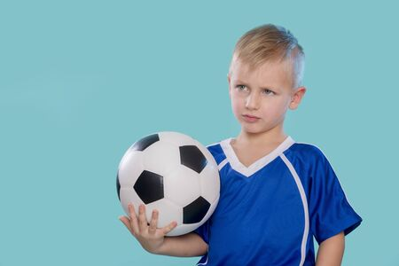 Happy little kid in sportswear holding a soccer ball isolated on blue background Banque d'images