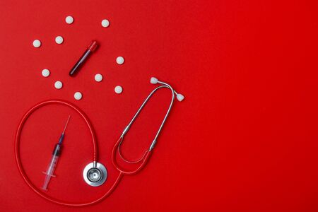 Virus Coronavirus blood test, pills, syringe and stethoscope on red copy space background for a banner