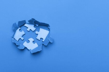 World Autism Awareness, concept with puzzle or jigsaw pattern in paper cut hole. Blue background