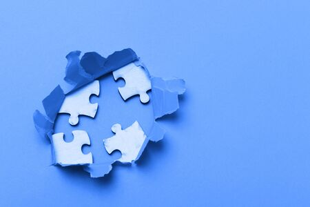 World Autism Awareness, concept with puzzle or jigsaw pattern in paper cut hole. Blue filter