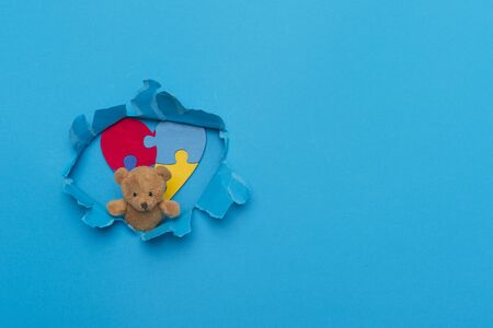 Teddy Bear Holding colorful Puzzle In Paper cut hole. World Autism Awareness Archivio Fotografico