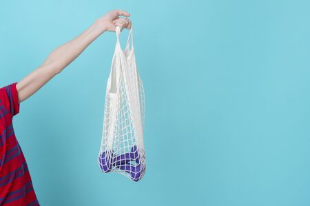 White mesh bag with dumbbells in hand on a blue background with copy space.