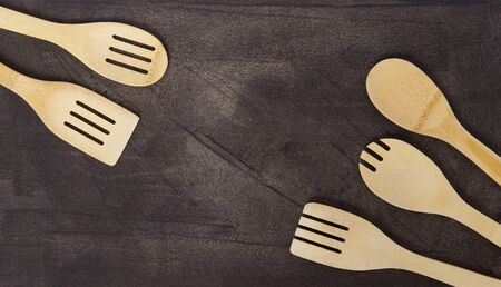 Top view of various wooden cooking utensils on grey background. Zero waste concept