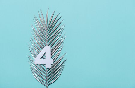 Number four shape with silver palm leaves on blue background. Summer concept. Flat lay. Top view