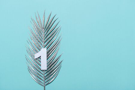 Number one shape with silver palm leaves on blue background. Summer concept. Flat lay. Top view