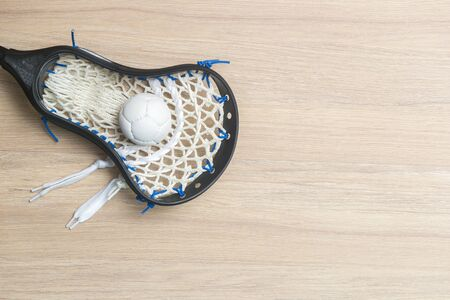 Lacrosse stick and white ball on wooden background. Lacross is a team sport