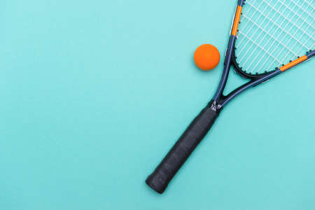 Close up of a squash ball and racket on blue background. Individual sport concept.