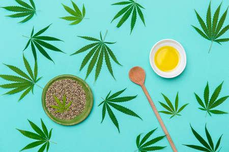 Green marijuana leaf, hemp seeds, wooden spoon and cannabis oil on mint color background. Alternative medicine. Vegetarian food concept