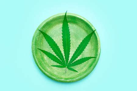 Green marijuana leaf, hemp seeds, wooden spoon on yellow color background. Alternative medicine. Vegetarian food concept 版權商用圖片