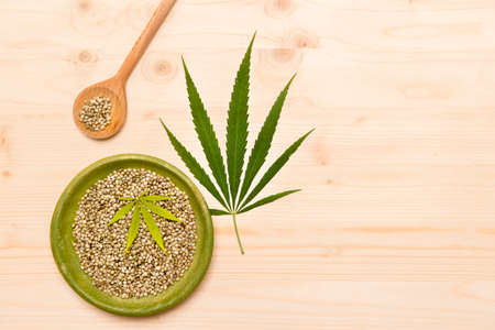 Green cannabis leaf and seeds on plate on wooden background. Vegetarian food concept