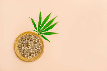 Green cannabis leaf and seeds on yellow plate on camel color background. Vegetarian food concept