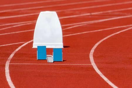Athletic start block on dark red tartan track. Individual sport concept