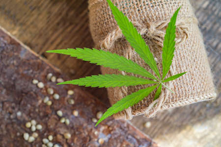 Hemp thread, medical marijuana leaves on wooden background. Using cannabis in fabric production and industry