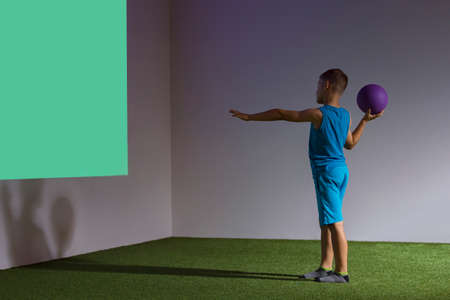 Kid playing interactive game projected to the wall. Ball games concept