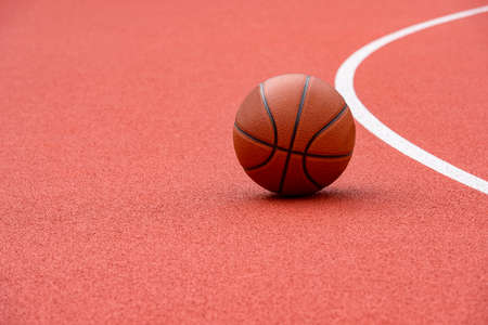 Close up on a white line in artificial red turf, on a street basketball, handball, volleyball, futsal, rugby, hockey and football field, in a sports background
