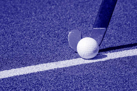 Field hockey stick and ball on green grass. Blue color filter