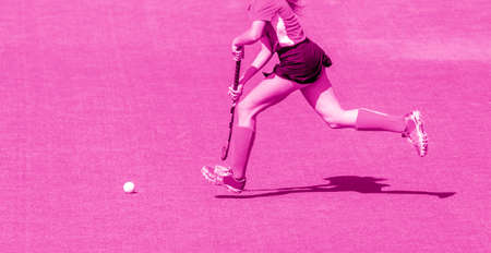 Young hockey player woman with ball in attack playing field hockey game. Pink color filter