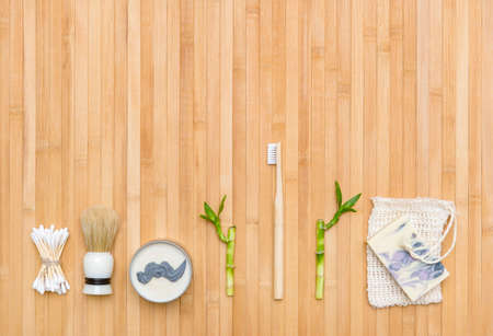 Flat lay shaving tools and bathroom accessories for man on bamboo wooden background. Zero waste concept.
