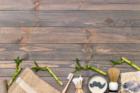 Flat lay shaving tools and bathroom accessories for man on wooden background. Zero waste concept.