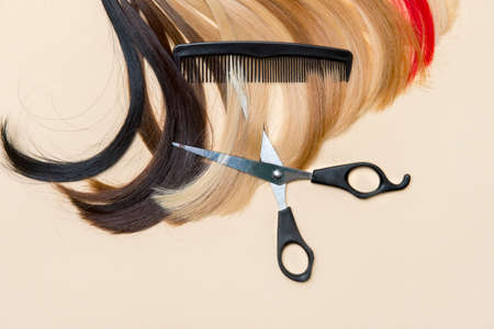 Hairdresser's scissors with comb and strand of hair on camel color background. Hairdresser service