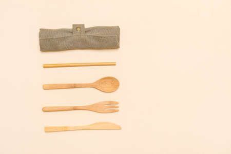 Set of Eco friendly bamboo cutlery on camel color background. Plastic free concept. Close-up, top view.
