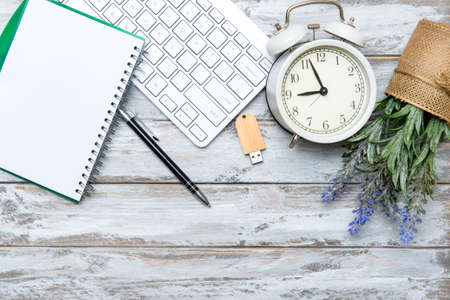 Home office workspace with computer keyboard, blank paper clipboard, alarm clock and green plant on wooden background. Flat lay, top view. Working home concept. 写真素材 - 158437913
