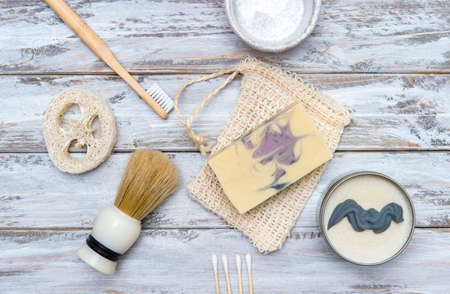 Flat lay of different hygiene and care items arranged on wooden background. Zero waste concept