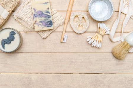 Top view of different hygiene and care items on cream color wooden surface, zero waste concept