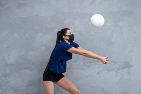 Young woman protective face mask with volleyball ball isolated on grey background. Protective masks against virus infection. Vintage color filter 写真素材 - 158436765