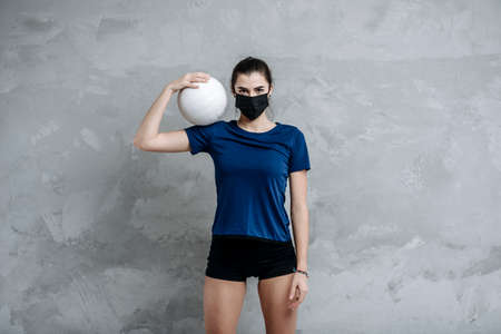 Young woman protective face mask with volleyball ball isolated on grey background. Protective masks against virus infection. Vintage color filter 写真素材 - 158436767