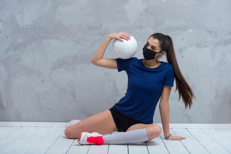 Young woman protective face mask with volleyball ball isolated on grey background. Protective masks against virus infection. Vintage color filter 写真素材 - 158436769