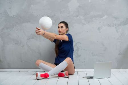 Young girl doing exercises with volleyball ball watching online tutorials on laptop. A sports coach leads an online lesson. Online workout concept. 写真素材 - 158436771